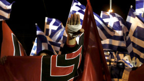 A supporter of Greece's far-right Golden Dawn party salutes in a Nazi style during a rally at central Syntagma square in Athens November 30, 2013. Hundreds of supporters gathered outside parliament on Saturday to protest the pre-trial detention of their leader Nikolaos Mihaloliakos, who faces charges of forming a criminal organisation. REUTERS/Yorgos Karahalis (GREECE - Tags: POLITICS CIVIL UNREST) - RTX15YY8