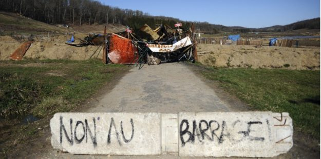 "A barricade reading ""No to the dam"" stands near the ""zone to defend"" (ZAD) area occupied by environmental activists protesting a dam project in the Sivens forest on March 5, 2015. Anti-dam activists say the project poses a huge environmental threat to the Sivens wetland while pro-dam farmers, who are blocking roads leading to the ZAD area, argue that the dam will provide much-needed irrigation for their fields. The Tarn department council is due to meet on March 6 to discuss alternatives to the original dam project. AFP PHOTO / REMY GABALDA"